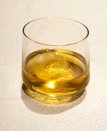 golden whiskey glass. Whisky on the rocks over a light textured background Banque d'images