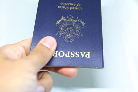 Image of a persons hand holding a passport over a white background