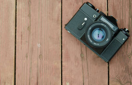 fond: Vintage camera while wearing the  lens rests on a wooden background Stock Photo