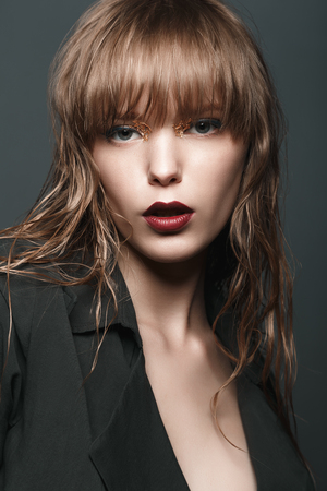dark red: Sexy blonde girl with red lips and gold on the eyes in a dark coat Stock Photo