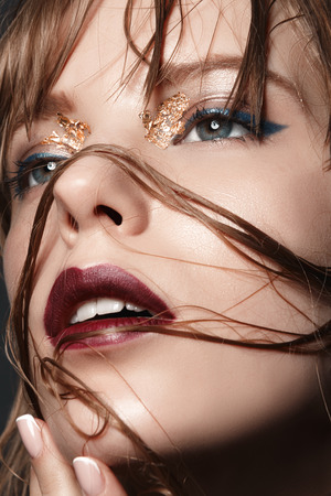 chica sexy: Muchacha rubia atractiva con los labios rojos y el oro en los ojos en un primer abrigo oscuro