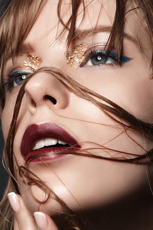 fille sexy: Sexy fille blonde avec des lèvres rouges et or sur les yeux dans un manteau noir closeup