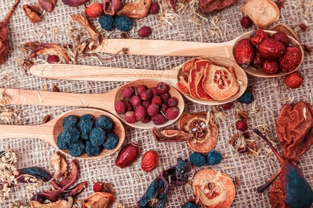 Dried fruit and berries in a wooden bowl on sacking background close-up macro