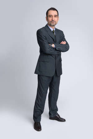 body image: Full body image of mature standing business man wearing dark suit, isolated over white background