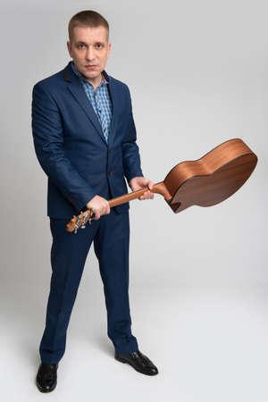 brandishing: businessman brandishing a guitar on a black background