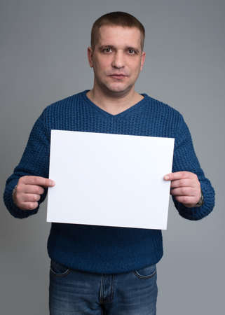 hoja en blanco: European-looking male holding a white sheet of paper on a gray background Foto de archivo
