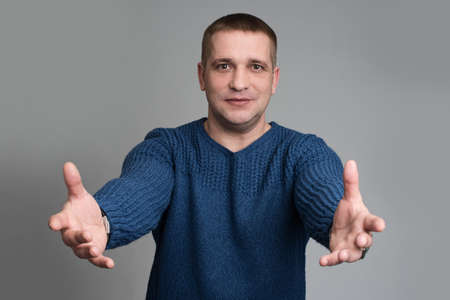 extrovert: generous 40s man grabbing or presenting something in empty hands forwards Stock Photo