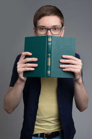 25s: Surprised young man in glasses looking out of the book