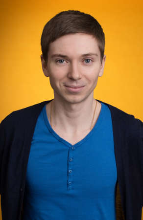 personable: Portrait of young man. Facial expression. Funny face. isolated on orange background
