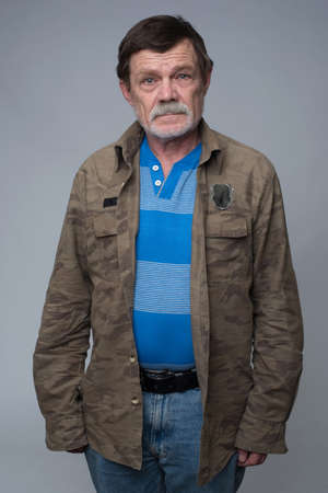 disapproving: Older man standing with crossed arms and showing disapproval