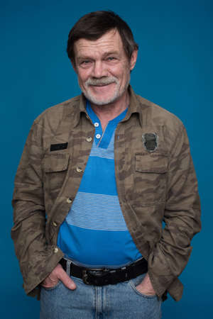 oldage: an elderly man with a beard, a mustache, holding hands in pockets isolated on a blue background Stock Photo