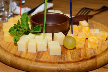 sorts: cubes of cheese of different varieties on a wooden tray