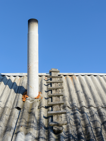 rudeness: old roof slate from the chimney on a background of blue sky Stock Photo