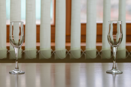 Two glasses on an empty table by the window