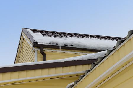 雪とつらら集合住宅の屋根の上でサイディングとおおわれ