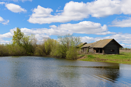 Old wooden house on the shore of the reservoir in the spring