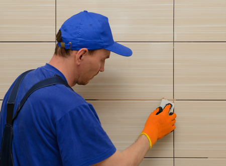 master-tiler blocks the seams between the tiles with beige cement grout Stok Fotoğraf