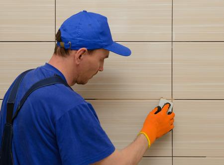 master-tiler blokkeert de naden tussen de tegels met beige cement grout Stockfoto