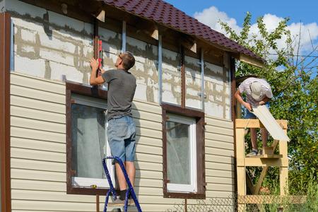 2017 년 8 월 6 일 : 두 노동자의 사진 비닐 사이딩과 건물의 외관을 커버. Cheboksary. 러시아 제국.