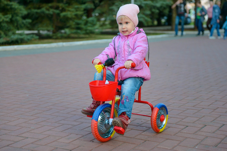 little girl in a jacket is riding in a park on a tricycle Stock Photo