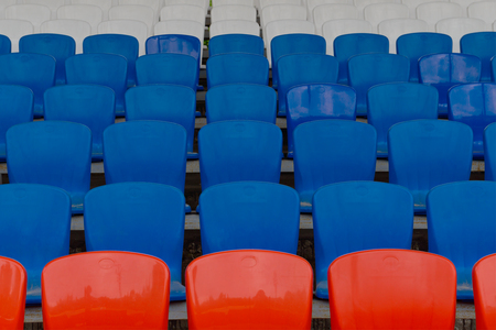 empty seats for spectators at the stadium painted in white blue and red colors of the national flag of Russia Stock Photo
