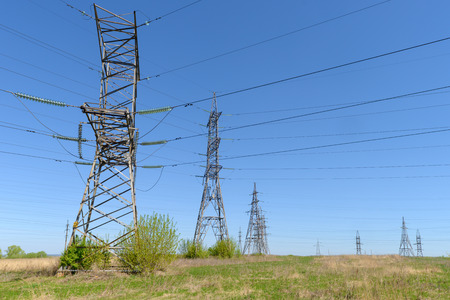 towers and power lines in the open field on a summer day