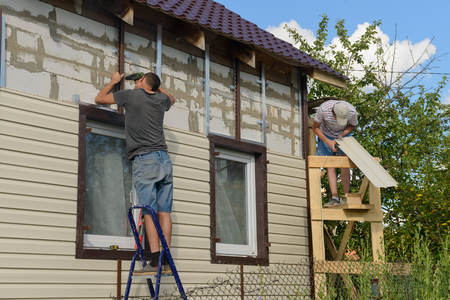 August 6, 2017: two workers polish the apartment building with vinyl siding. Moskakassy. Chuvashy. Russia. Banque d'images - 105851050