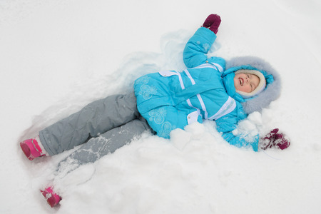 little girl in blue winter clothes is lying on the snow and smiling 스톡 콘텐츠