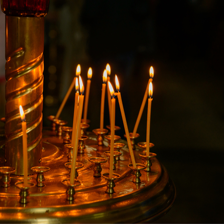 burning candles on a gilded surface in an orthodox church