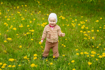 A small child laughs among a field of yellow dandelions