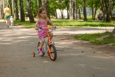 The little girl rides a childrens four-wheeled bike in the park. Zdjęcie Seryjne