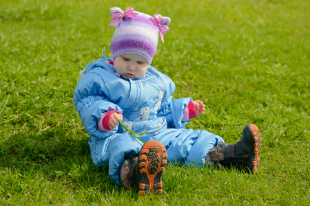 small child in a blue jumpsuit sits on young grass and plays with a blade of grass in the spring afternoon
