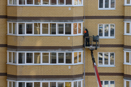 worker on an autotower repairs the facade of an apartment brick residential building
