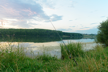 Evening summer landscape with a fishing rod on the lake
