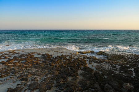 evening sea landscape with turquoise sea and rocky shore