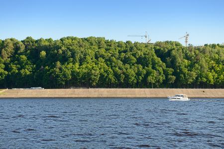 Powerboat sailing down the river along a concrete embankment with a green forest and tower cranes on the horizon