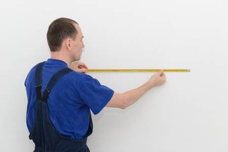 Worker in overalls measures the distance on a white wall using a tape measure