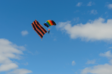 Parashutist with a multi-colored parachute and a flag in the form of the St. George ribbon