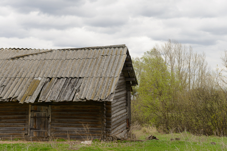 Old abandoned log house among the trees in cloudy weather