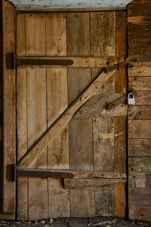Old collapsing wooden door with rusty hinges and a padlock Zdjęcie Seryjne