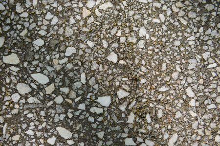 texture of old concrete wall with marble stones with lichen