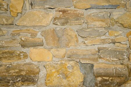 the surface of the old wall of beige stones