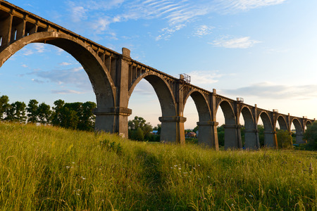 Old arch bridge over a gully overgrown with grass in the summer evening Publikacyjne