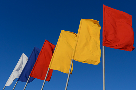 White, blue, red and yellow flags develop in the wind against a blue sky.