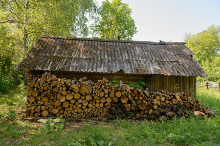 A log wall for firewood in an old wooden house near the cemetery