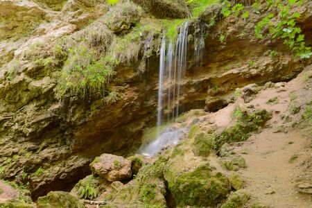 Small waterfall in the summer rocky slope