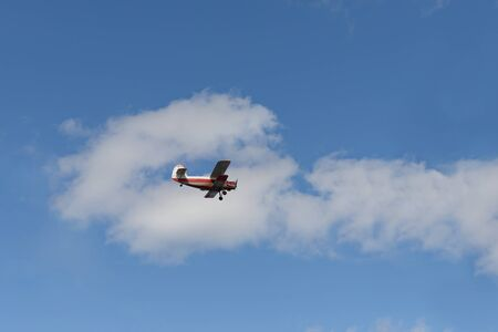 Old biplane flying in the blue sky with clouds