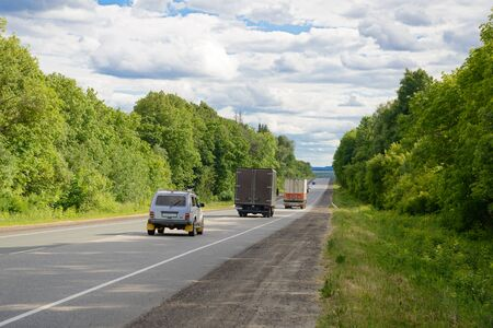 Cars and trucks ride along the highway along a green forest Zdjęcie Seryjne