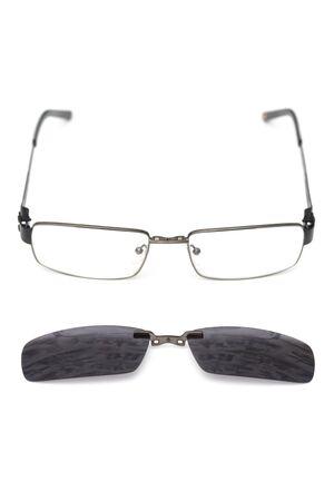 Glasses with removable sun glasses lie on a white background. Zdjęcie Seryjne