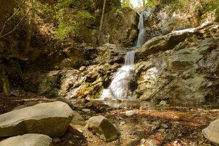 Forest summer landscape with a waterfall in a rocky hill